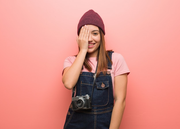 Young cute photographer woman shouting happy and covering face with hand