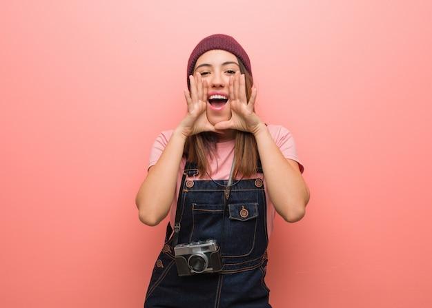 Молодая милая женщина фотографа крича что-то счастливое к фронту