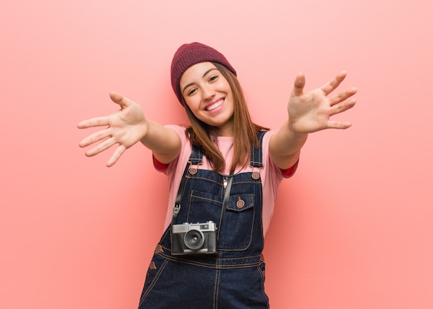 Young cute photographer woman very happy giving a hug to the front