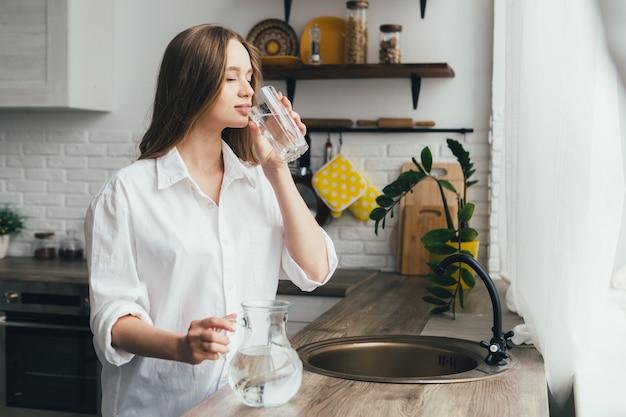 Молодая милая беременная девушка пьет чистую воду на кухне