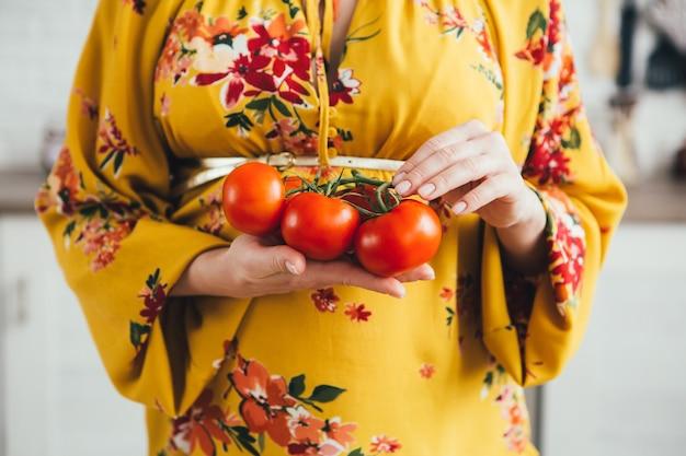 キッチンで野菜サラダを準備する若いかわいい妊娠中の女の子