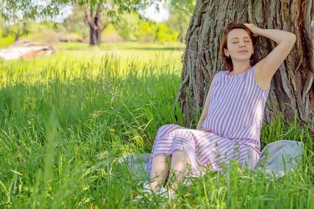 屋外で自然を楽しんでいる日陰の木の下に座っている若いかわいい妊娠中の女性、赤ちゃんを期待して幸せな妊娠中の女性の肖像画