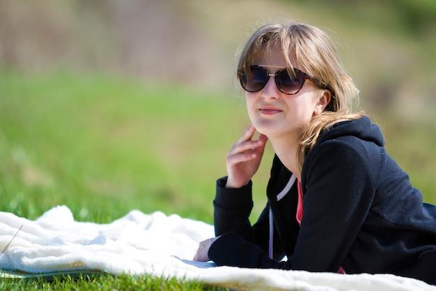 Молодая милая довольно блондинка в черном свитере и темных очках лежит на белом полотенце на зеленой траве, наслаждаясь природой и теплым солнечным днем, счастливо улыбаясь