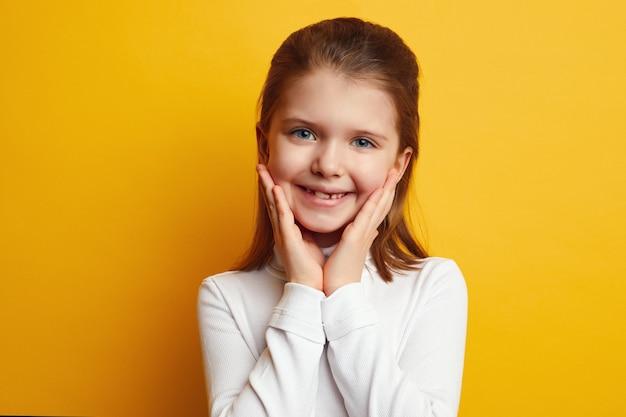 Молодая симпатичная ученица держит руки на щеках и улыбается у желтой стены