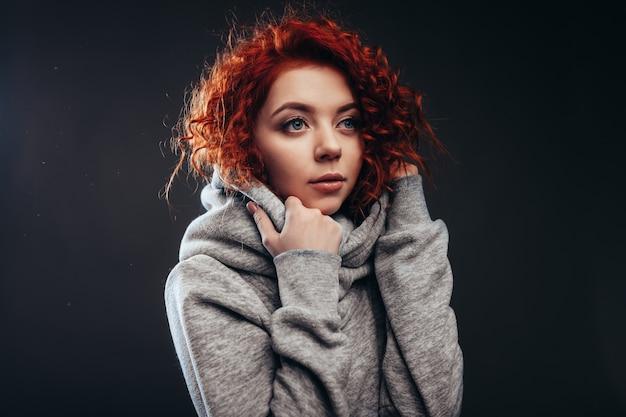 青い目を持つ若いかわいい赤毛の女の子はクローズアップの肖像画を灰色のパーカーに身を包んだ