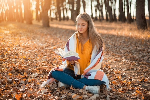 Young cute schoolgirl sitting in plaid in autumn forest and reading a book
