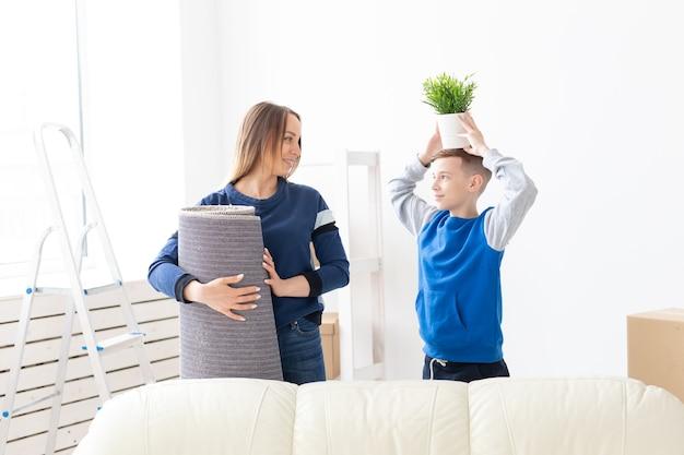 젊은 귀여운 미혼모와 아들은 녹색 냄비를 들고 새 집으로 이사하는 것에 대해 행복합니다.