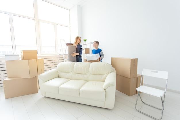 젊은 귀여운 미혼모와 아들은 녹색 냄비를 들고 새 집으로 이사하는 것에 대해 행복하고