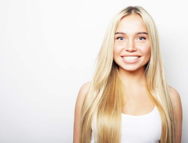 Молодая милая улыбающаяся блондинка на белом фоне