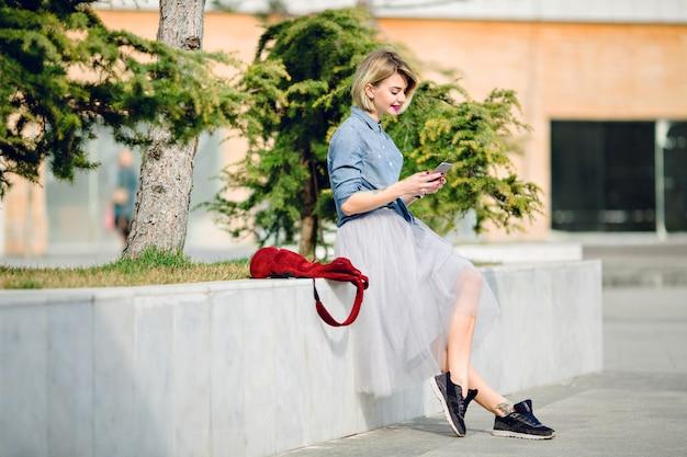 Giovane donna bionda sorridente carina con i capelli corti e labbra rosa brillante seduto in un parco e leggendo un messaggio sul suo smartphone