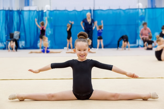 Young cute smiling girl doing split in gymnastic hall.
