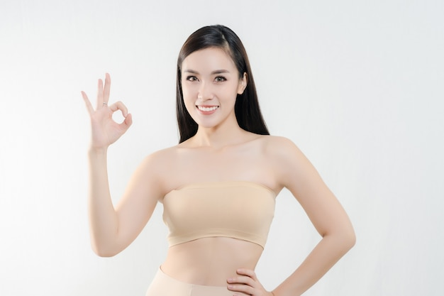 Young cute smiling girl with perfect skin showing ok sign