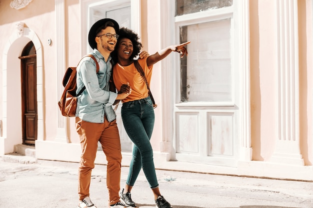 若いかわいい笑顔の多文化ヒップスターのカップルは、女性が何かを指している間、抱き締めて通りを歩いています。多様性の概念。