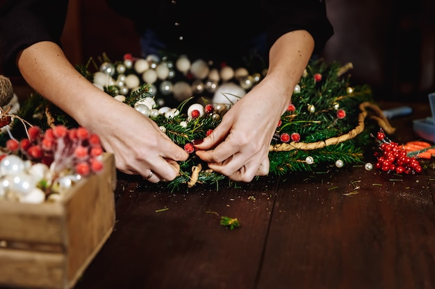 Young cute smiling woman designer preparing christmas evergreen tree wreath, manufacturer of christmas decor with their own hands, christmas wreath for the holiday, the new year celebration.