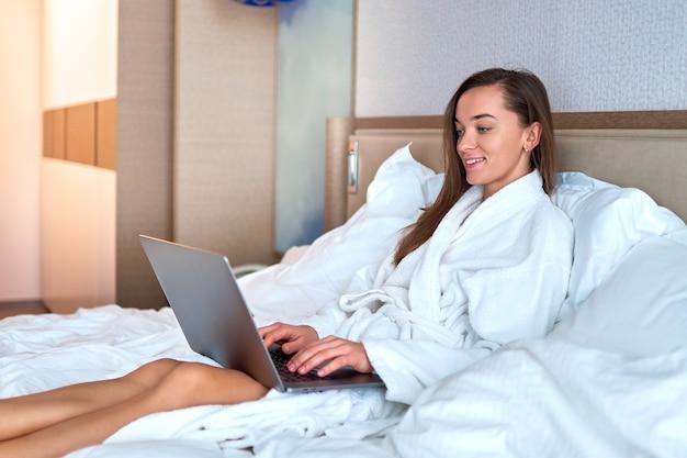 ホテルの部屋からベッドの上のコンピューターでオンラインで作業している白いバスローブを着た若いかわいい笑顔の女性フリーランサー。簡単なライフスタイル