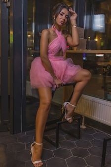 Young cute stylish woman in beautiful shiny dress on dark interior background restaurant. pretty female posing for photo advertising business.