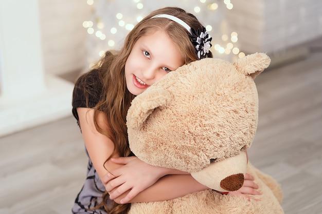 若いかわいい10代の少女は、新年の装飾が施されたインテリアで大きな柔らかいテディベアを抱擁します。