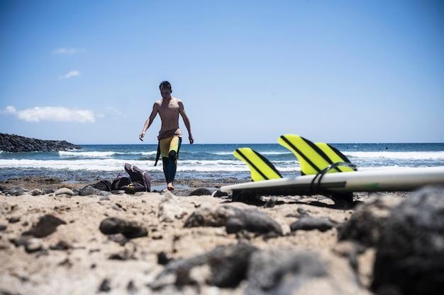 행복 대안 열대 해변을위한 바위 휴가 및 수상 스포츠 활동에 파도 테이블과 지느러미에 서핑 세션 후 물에서 나오는 젊은 귀여운 십 대 남성 서퍼 프리미엄 사진