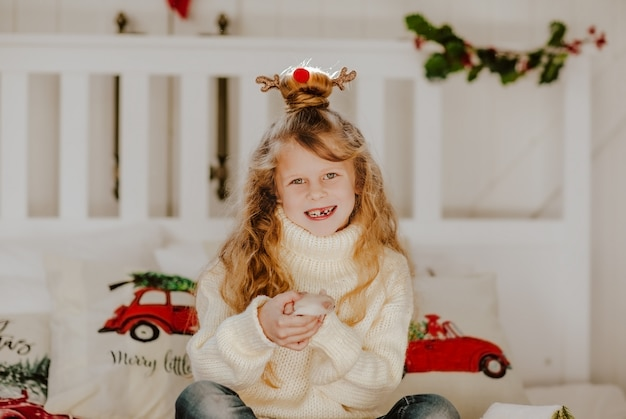 Young cute toothless girl in white sweater and hairdress like christmas deer