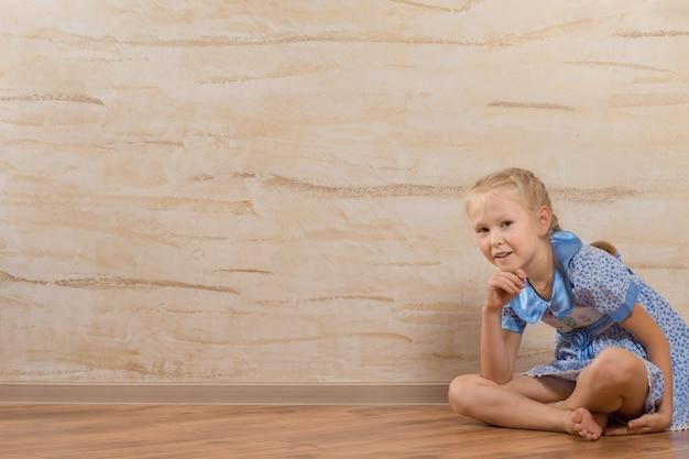 Молодая милая белая девушка, сидя на полу, изолированные на деревянных стенах
