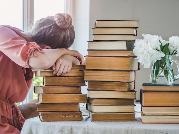 若い、かわいい女性とヴィンテージの本のスタック。クローズアップ、孤立した背景。スタジオ写真。学習と教育のコンセプト