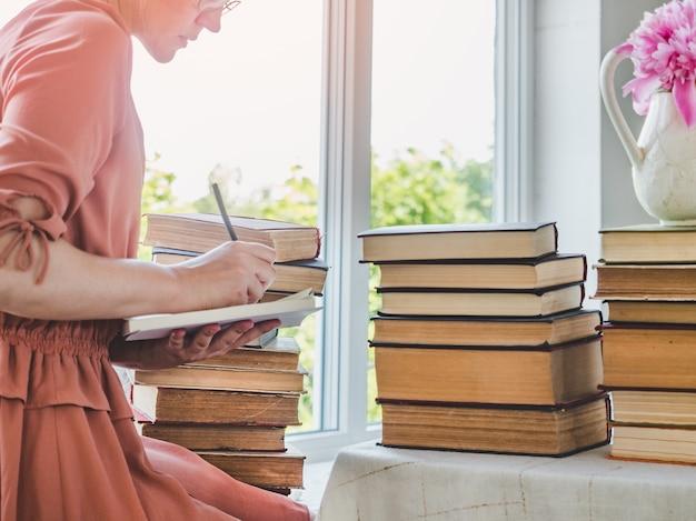 若い、かわいい女性とヴィンテージの本のスタック