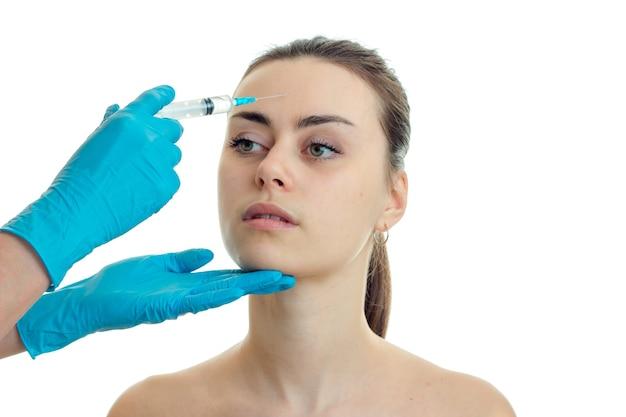 Молодая милая женщина у пластического хирурга изолирована на белой стене