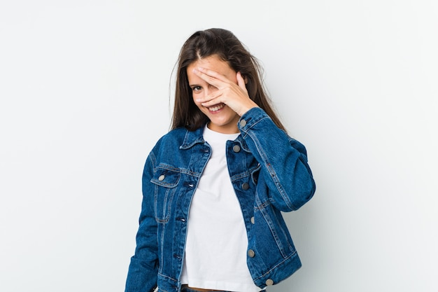 Young cute woman blink at the camera through fingers, embarrassed covering face.