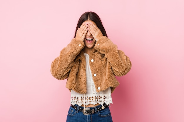 Young cute woman covers eyes with hands, smiles broadly waiting for a surprise.