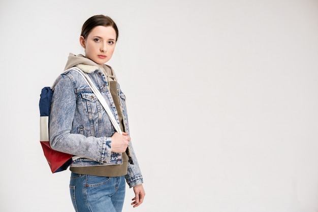 Young cute woman in a denim jacket and with a backpack posing on a white wall