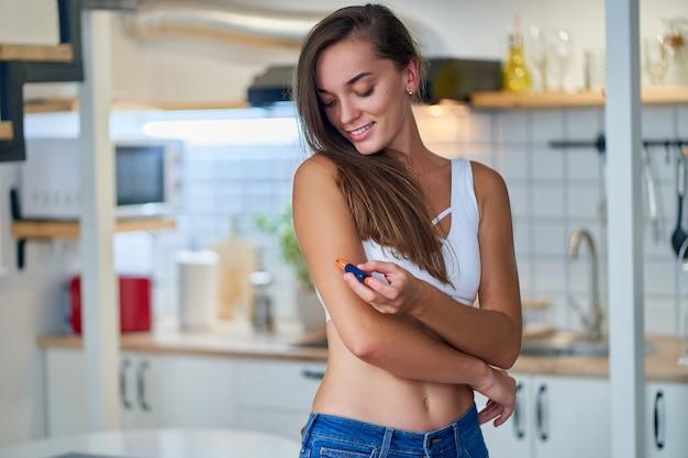 Молодая милая женщина диабетик дает инъекцию инсулина в плечо с помощью ручки инсулина дома. лечение и контроль диабета, здравоохранение
