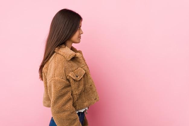 Young cute woman gazing left, sideways pose.
