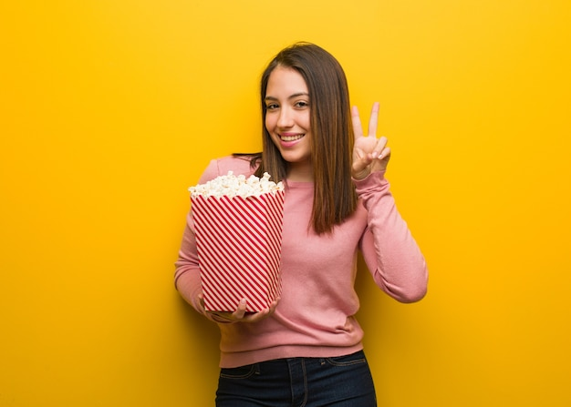 Молодая милая женщина, держащая ведро с попкорном, весело и счастлива, делая жест победы