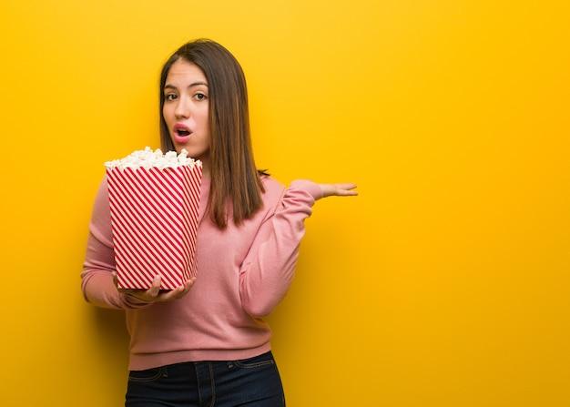 Молодая милая женщина держит ведро попкорна, держа что-то на ладони