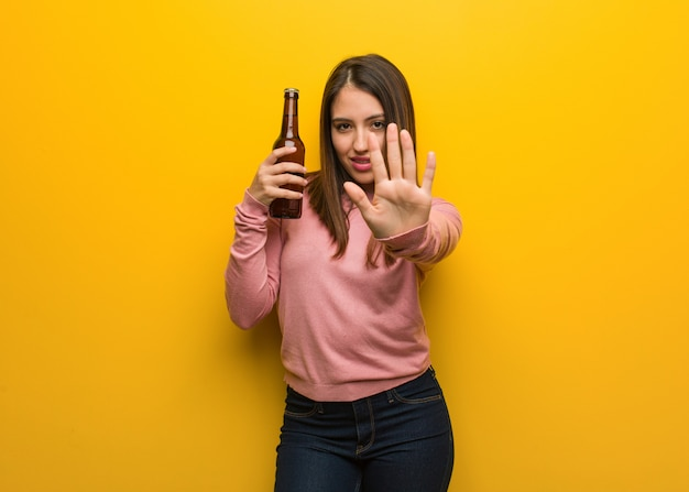 Young cute woman holding a beer putting hand in front