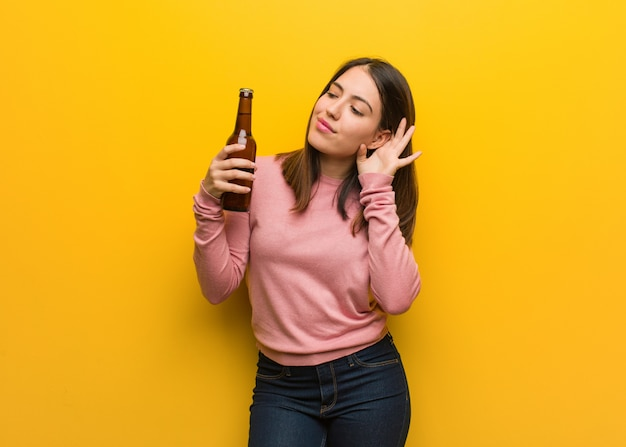 Young cute woman holding a beer try to listening a gossip