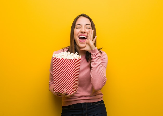 Young cute woman holding a popcorn bucket shouting something happy to the front