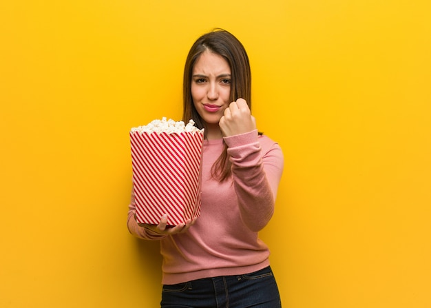 Young cute woman holding a popcorn bucket showing fist to front, angry expression