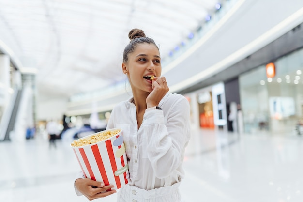 Молодая милая женщина, держащая попкорн на фоне торгового центра