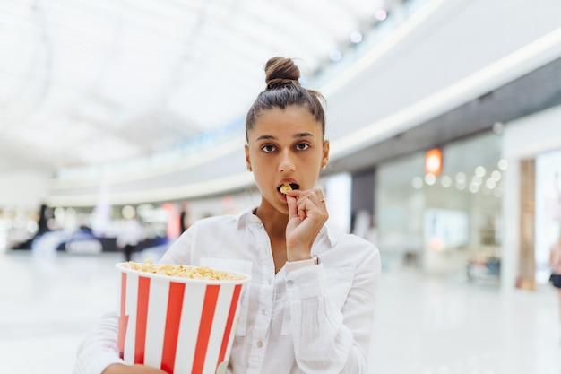 Giovane donna carina che tiene popcorn nel centro commerciale