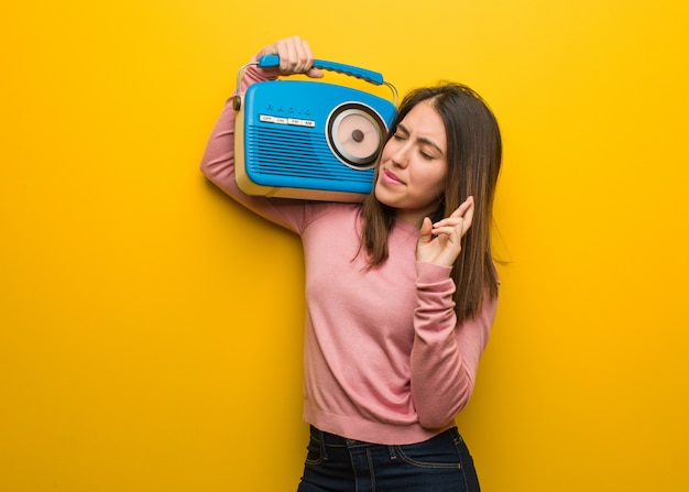 Young cute woman holding a vintage radio crossing fingers for having luck