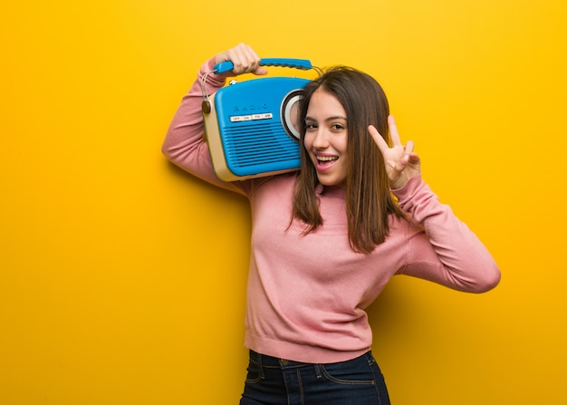 Young cute woman holding a vintage radio fun and happy doing a gesture of victory