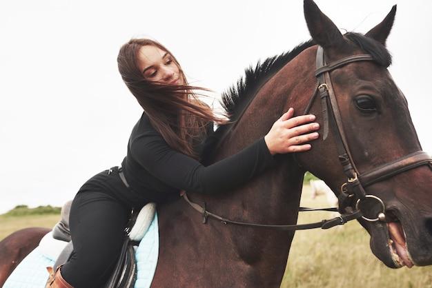 若いかわいい女性がまたがって座っている間彼女の馬を抱き締めます。彼女は動物が好き