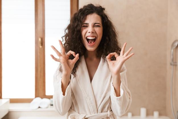 Молодая милая женщина в ванной, делая хорошо жест