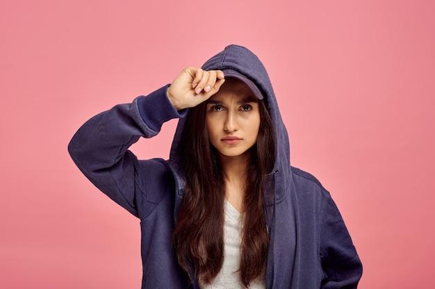 パーカー、ピンクの壁、感情の若いかわいい女性
