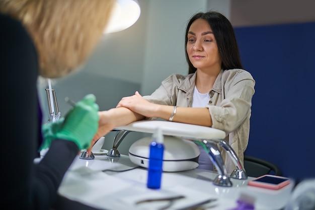 Молодая милая женщина в салоне ногтей, получающая маникюр мастером маникюра. бережный уход за ногтями