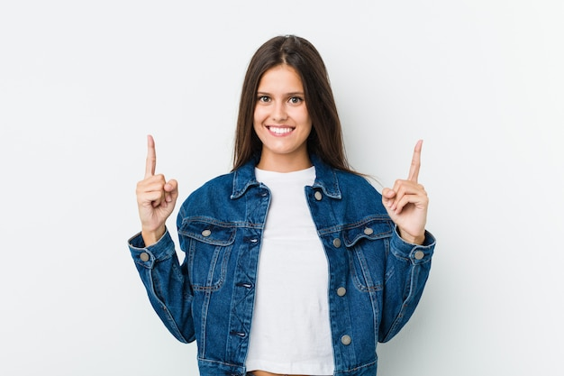 Young cute woman indicates with both fore fingers up showing a blank space.