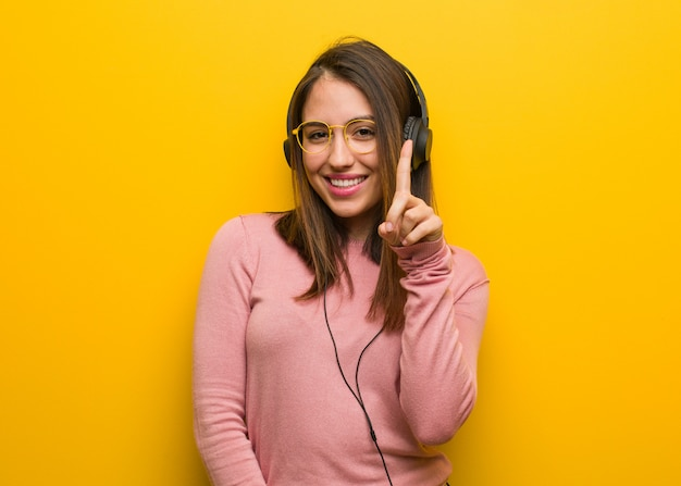 Young cute woman listening to music showing number one