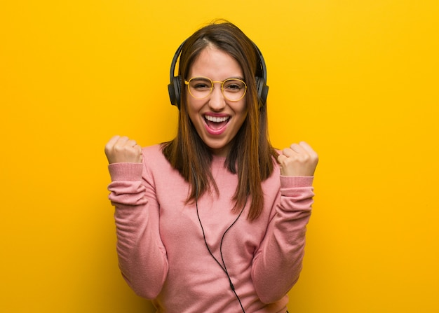 Young cute woman listening to music surprised and shocked