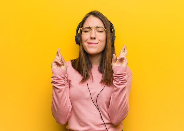 幸運のために指を交差させる音楽を聞いている若いかわいい女性